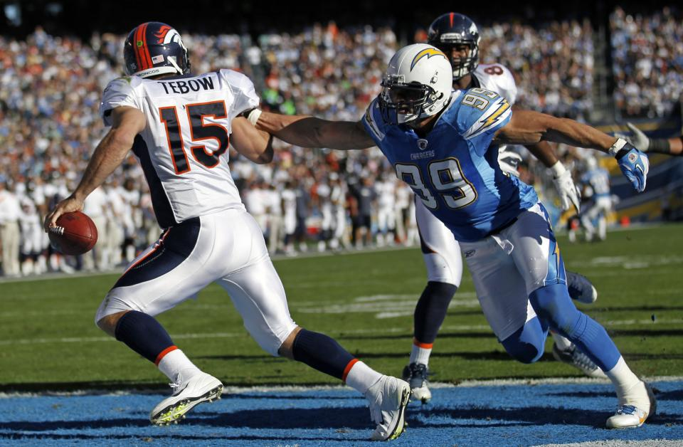 Denver Broncos quarterback Tim Tebow (15) runs under pressure from San Diego Chargers outside linebacker Travis LaBoy during the first half of an NFL football game on Sunday, Nov. 27, 2011, in San Diego. (AP Photo/Lenny Ignelzi)