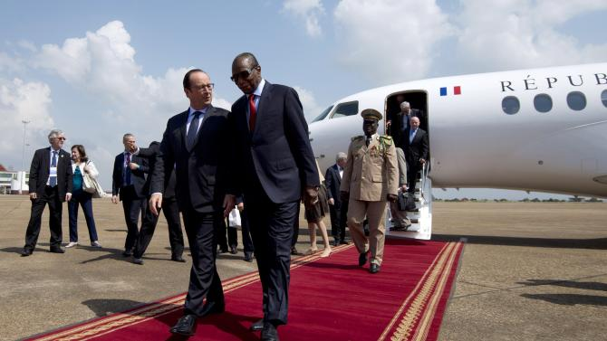 French president Hollande walks with Guinea's President Alpha Omar Conde at the Airport in Conakry