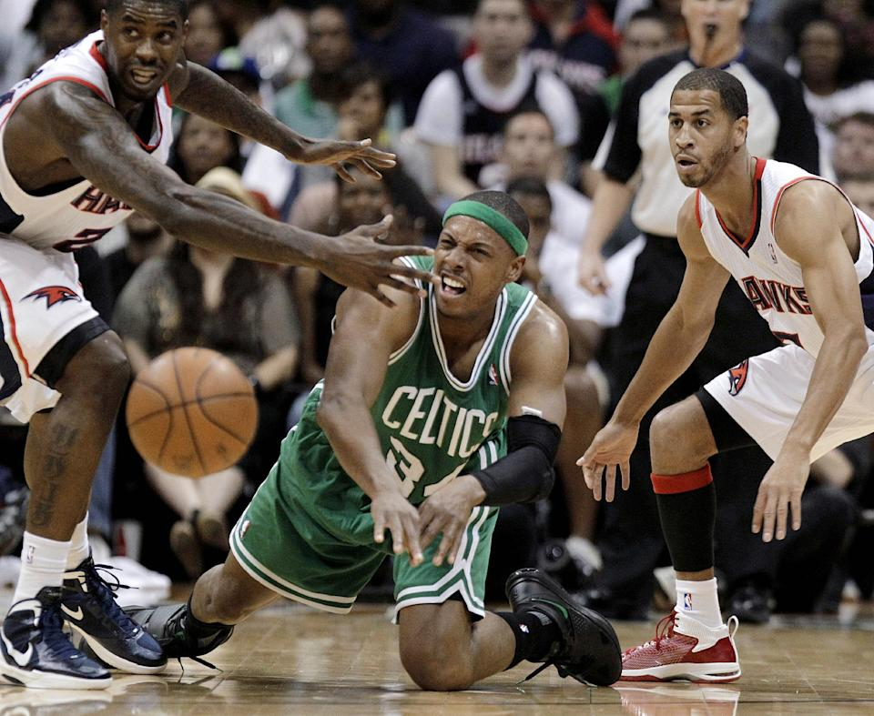 Boston Celtics' Paul Pierce, center, passes the ball as Atlanta Hawks' Marvin Williams, left, and Jannero Pargo defend durign the second quarter of Game 1 of an opening-round NBA basketball playoff series, Sunday, April 29, 2012, in Atlanta. (AP Photo/David Goldman)