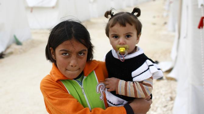 A Kurdish refugee girl from the Syrian town of Kobani carries a baby at a refugee camp in the border town of Suruc