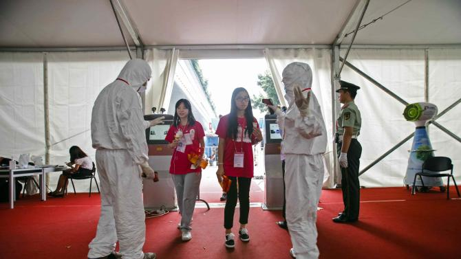 People have their temperature taken at the entrance of Canton Fair in Guangzhou