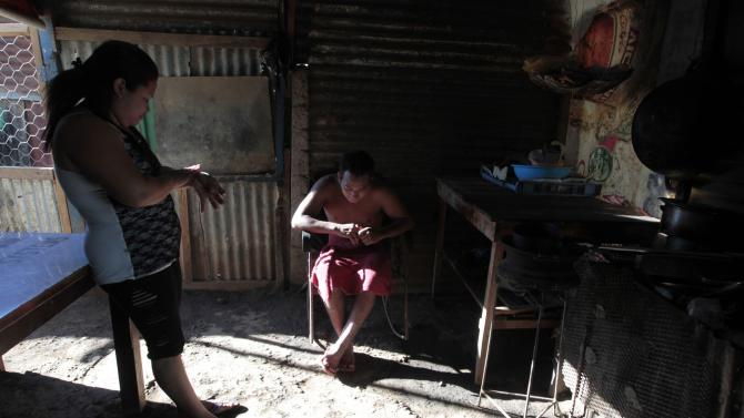 uan Lopez, a chikungunya virus victim, sits inside his kitchen while a Health Ministry worker (not pictured) fumigates against mosquitoes that carry the virus, in Managua