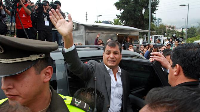 President Rafael Correa waves to supporters as he leaves a polling station after voting in Quito, Ecuador, Sunday, Feb. 17, 2013. President Rafael Correa gestures to photographers as he votes at a polling station in Quito, Ecuador, Sunday, Feb. 17, 2013.  Ecuadoreans  elect president,  vice-president and National Assembly members Sunday with Correa highly favored to win a second re-election.(AP Photo/Martin Jaramillo)