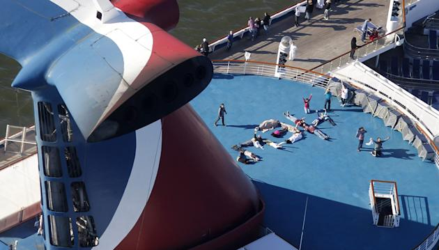 "Passengers spell out the word ""HELP"" aboard the disabled Carnival Lines cruise ship Triumph as it is towed to harbor off Mobile Bay, Ala., Thursday, Feb. 14, 2013. The ship with more than 4,200 passen"