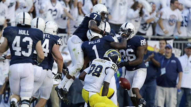 The Penn State defense celebrates an interception by Penn State defensive end Anthony Zettel (98) behind Michigan quarterback Devin Gardner (98) and Michigan offensive linesman Chris Bryant (58) during the second quarter an NCAA college football game in State College, Pa., Saturday, Oct. 12, 2013. (AP Photo/Gene J. Puskar)