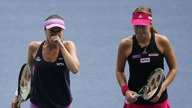 Martina Hingis of Switzerland and her partner and compatriot Belinda Bencic react after losing a point during their Pan Pacific Open women's doubles tennis match against Cara Black of Zimbabwe and Sania Mirza of India in Tokyo