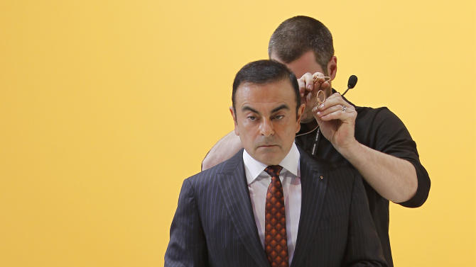CEO of Renault and Nissan Carlos Ghosn looks on as technicians prepare him during the presentation of the new Renault Captur during the first media day of the 83rd Geneva International Motor Show, Switzerland, Tuesday, March 5, 2013. The Motor Show will open its gates to the public from March 7 to 17.  (AP Photo/Laurent Cipriani)