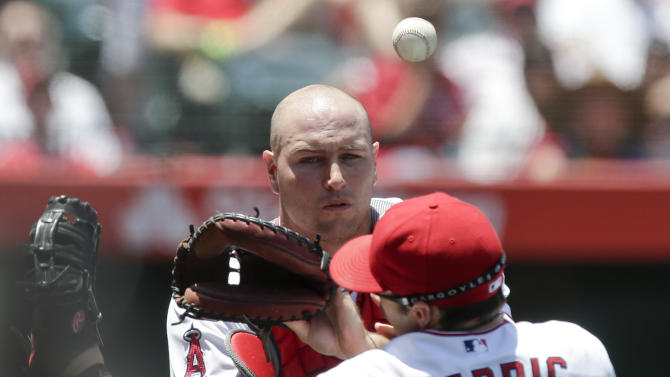 Los Angeles Angels catcher Chris Iannetta, top, collides with first baseman  Brendan Harris trying for a could ball hit by New York Yankees shortstop Jayson Nix  during the second inning of a baseball game in Anaheim, Calif., Sunday, June 16, 2013. (AP Photo/Chris Carlson)