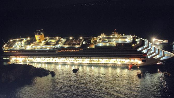FILE - In this file photo taken Friday, Jan. 13, 2012, the luxury cruise ship Costa Concordia lays on its starboard side after it ran aground off the coast of the Isola del Giglio island, Italy. As if the nightmares, flashbacks and anxiety weren't enough, passengers who survived the terrifying grounding and capsizing of the Costa Concordia off Tuscany have come in for a rude shock as they mark the first anniversary of the disaster on Sunday, Jan. 13, 2013. Ship owner Costa Crociere SpA, the Italian unit of Miami-based Carnival Corp., sent several passengers a letter telling them they weren't welcome at the official anniversary ceremonies on the island of Giglio where the hulking ship still rests. Costa says the day is focused on the families of the 32 people who died Jan. 13, 2012, not the 4,200 passengers and crew who survived.  (AP Photo/Giuseppe Modesti, File)