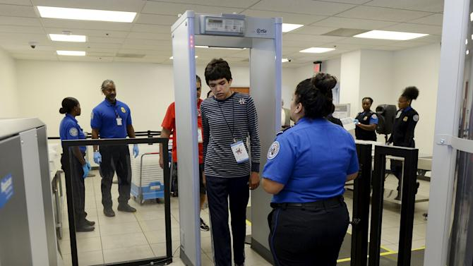 """Autistic boy Jeffery Jr. Simonton walks through the metal detector while a TSA agent looks on during the """"Flight Experience Program"""" event at Los Angeles International Airport"""