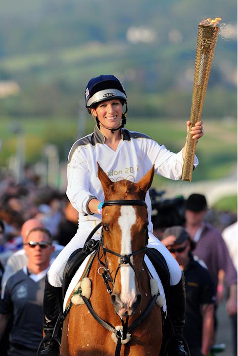 This photograph made available by LOCOG shows  Britain's Queens Elizabeth's grand-daughter  Zara Phillips carrying  the Olympic Flame at the end of day 5 of the torch relay at Cheltenham Racecourse in