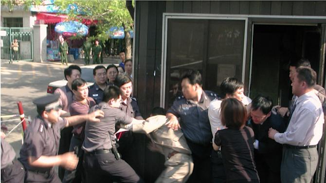 In this June 13, 2002 photo, Chinese security officers and officials at South Korean Embassy in Beijing scuffle in front of a police guard box next to the embassy's main gate as the security officers attempted to drag away a North Korean asylum seeker. Two North Koreans entered the embassy on June 13, 2002 amid a spate of asylum bids by North Koreans, but Chinese guards dragged an asylum-seeker from the visa office after punching and kicking diplomats who tried to block them. North Korea's prison population has swelled in recent years with those caught fleeing the country under a crackdown on defections by young leader Kim Jong Un, according to defectors living in South Korea and researchers who study Pyongyang's notorious network of labor camps and detention centers. (AP Photo/Kyodo News) JAPAN OUT, MANDATORY CREDIT