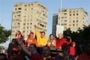 Venezuela's President Hugo Chavez waves at supporters during a campaign rally in Guarenas