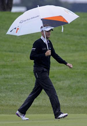 David Lynn walks the first fairway under an umbrella as rain falls during the final round of the BMW Championship golf tournament at Conway Farms Golf Club in Lake Forest, Ill., Sunday Sept. 15, 2013. (AP Photo/Matt Marton)