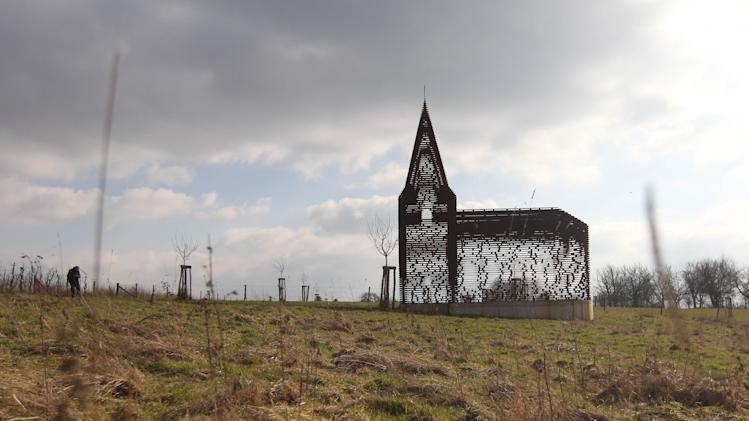 In this Feb. 20, 2013 file photo, a see-through church is pictured on a hilltop in Borgloon, 80 km (50 miles) East of Brussels. The artistic vision of the church is made of rusty steel beams separated by gaps, and its austere beauty won it an international architecture prize. Yet the eerie desolation of the see-through installation has also turned into a reflection on the state of Roman Catholicism on a religion-weary continent where real churches, like the dozen dotting the hills of this verdant area, increasingly lose their flock and function. (AP Photo/Yves Logghe, file)