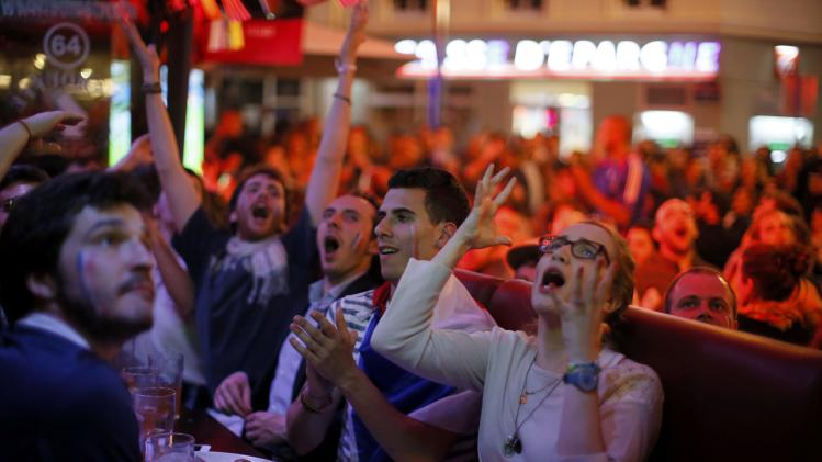 France team soccer fans react during dinner as they gather to watch a live broadcast of the 2014 World Cup Group E soccer match between Ecuador and France at the Maracana stadium in Rio de Janeiro, at a cafe in Paris