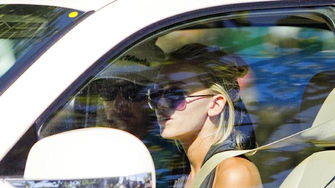 Paulina Gretzky, right, and Dustin Johnson drive away from the Waialae Country Club after Johnson withdrew from the Sony Open Golf Tournament after playing nine holes in the second round on Friday, Jan. 11, 2012, in Honolulu. Johnson withdrew because of the flu. (AP Photo/Marco Garcia)