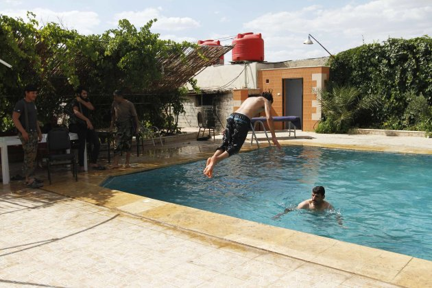 A member of the Free Syrian Army jumps into a swimming pool in Aleppo