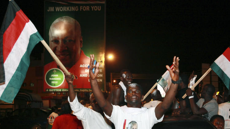 Supporters of President John Dramani Mahama celebrate in the streets after he was declared the winner of Ghana's presidential election, in Accra, Ghana, Sunday, Dec. 9, 2012. President Mahama on Sunday was declared the winner despite widespread technical glitches with the machines used to identify voters and protests by the country's opposition which claims the vote was rigged. (AP Photo/Christian Thompson)