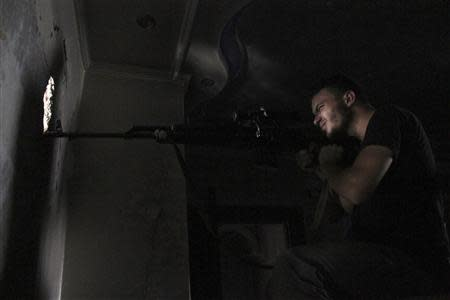 A Free Syrian Army sniper is seen in shooting position in Aleppo's Al-Ezaa front line
