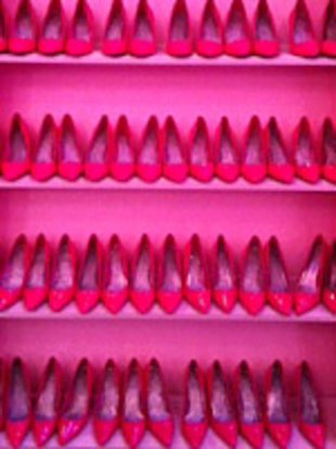 The inside of Barbie's Dream Closet is bathed in pink, right down to the three stories of pink pumps on the wall.