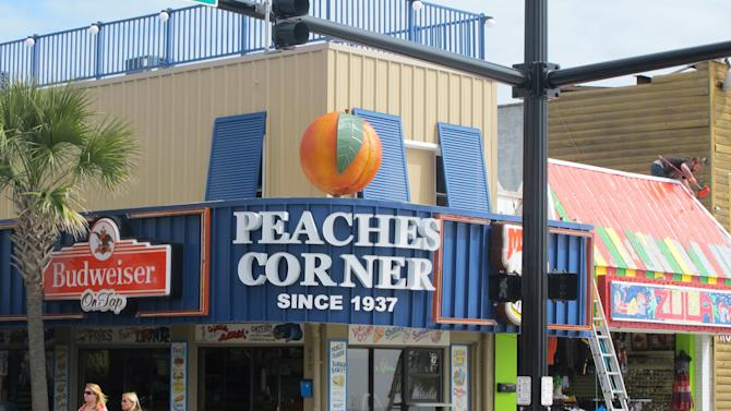 In this March 7, 2012 photo, visitors walk past the Peaches Corner restaurant in downtown Myrtle Beach, S.C. The restaurant, long a Myrtle Beach landmark, recently underwent a renovation and now features a revolving peach on its facade. (AP Photo/Bruce Smith)