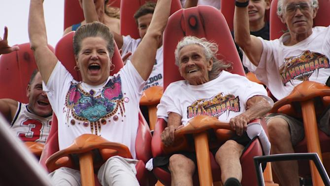 In this photo provided by Kings Island, Thelma Gratsch, center, celebrates her 90th birthday Friday, July 13, 2012, by riding her favorite roller coaster, Diamondback, at Kings Island amusement park in Mason, Ohio.Gratsch estimates she has ridden the tallest and fastest roller coaster at Kings Island more than 100 times since the ride opened in 2009.(AP Photo Kings Island, Don Helbig)