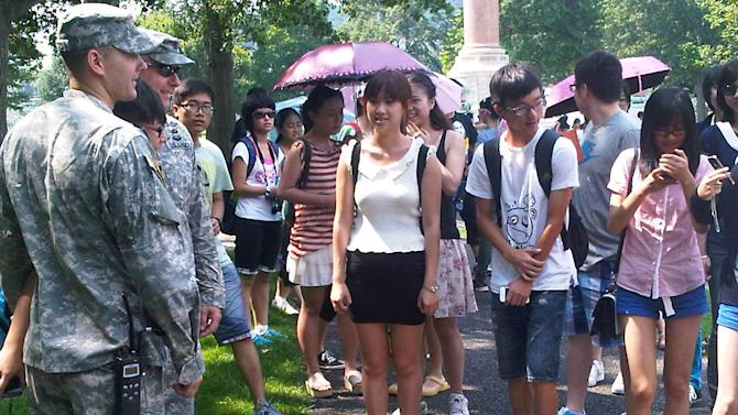 In this photo of Aug. 3, 2012, a tourist poses with cadets for a photo as others wait their turn during a tour of the U.S. Military Academy at West Point, N.Y.  Suburbs in the New York metropolitan area are stepping up their efforts to attract tourist dollars, not by competing with New York City, but by marketing themselves as complementary destinations. (AP Photo/Jim Fitzgerald)