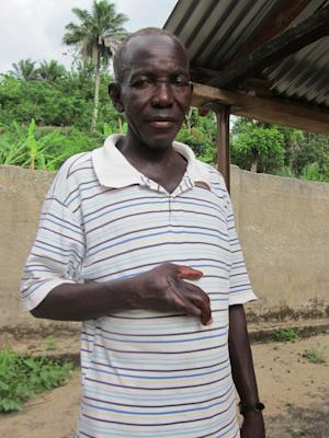 """In this Wednesday, April 25, 2012 photo, Samuel Komba, whose right hand was damaged in 1998 when attacking rebel soldiers tried to amputate it after catching him fleeing, poses for a picture in the village of Tombodu, Kono district, Sierra Leone. The 58-year-old, one of only two survivors of the 1998 attack, said he took solace Thursday from ex-Liberian President Charles Taylor's conviction for his role in Sierra Leone's brutal war. """"The whole world will know today what Charles Taylor did, and we are happy,"""" he said from Tombodu, where many who survived the fighting were enslaved as diamond miners. (AP Photo/Jessica McDiarmid)"""