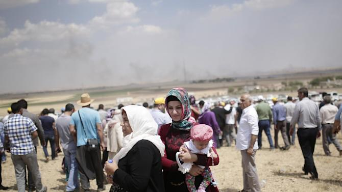 People standing on the Turkish side of the border with Syria, on the outskirts of Suruc, Turkey, watch as smoke rises over Kobani, in Syria, Saturday, June 27, 2015. Fighting raged into the night Friday between Kurdish fighters and Islamic State militants in the Syrian border town of Kobani, also known as Ayn Arab, as reports mounted that at least 120 civilians, including women and children, have been killed by the extremist group since it launched a new offensive on the strategic town the previous day. (AP Photo/Yasin Akgul)