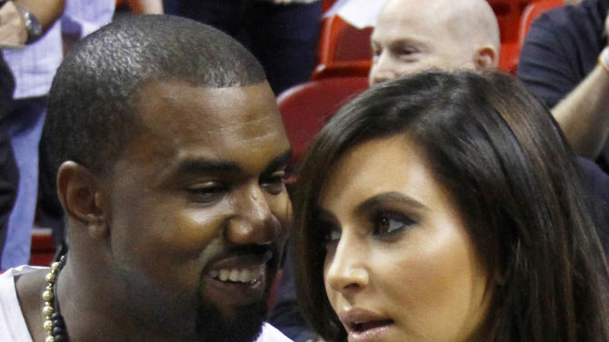 FILE - In this Dec. 6, 2012 file photo singer Kanye West, left, talks to his girlfriend Kim Kardashian before an NBA basketball game between the Miami Heat and the New York Knicks in Miami. Authorities say an airline employee is being investigated for allowing West and Kardashian to bypass a security checkpoint at New York's Kennedy Airport. (AP Photo/Alan Diaz, File)