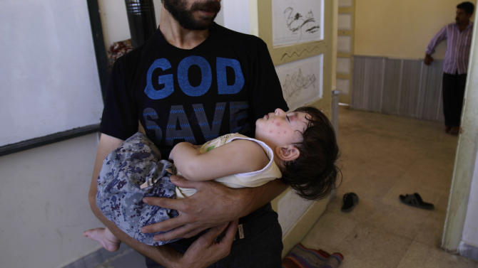 A Syrian man who fled his home in Aleppo 32 days ago due to government shelling, carries his sleeping son, who's face is covered with mosquito bites, back to a classroom of a school where they take refuge, in Suran, on the outskirts of Aleppo, Syria, Sunday, Sept. 16, 2012. (AP Photo/Muhammed Muheisen)