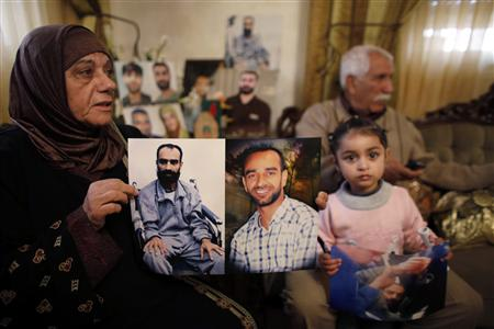 Layla al-Issawi holds a picture of her son Samer, held in an Israeli prison, at her home in East Jerusalem