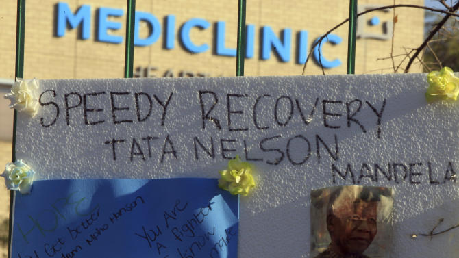 A print of Nelson Mandela and get-well messages hanged outside the Mediclinic Heart Hospital where former South African President Nelson Mandela is being treated in Pretoria, South Africa Monday, June 24, 2013. Mandela's health has deteriorated and he is now in critical condition, the South African government said. (AP Photo/Themba Hadebe)