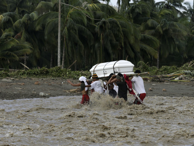 Relatives cross a river to bury their loved one, who died in a flash flood caused by Typhoon Bopha, Thursday, Dec. 6, 2012, in New Bataan township, Compostela Valley in southern Philippines.  The powe