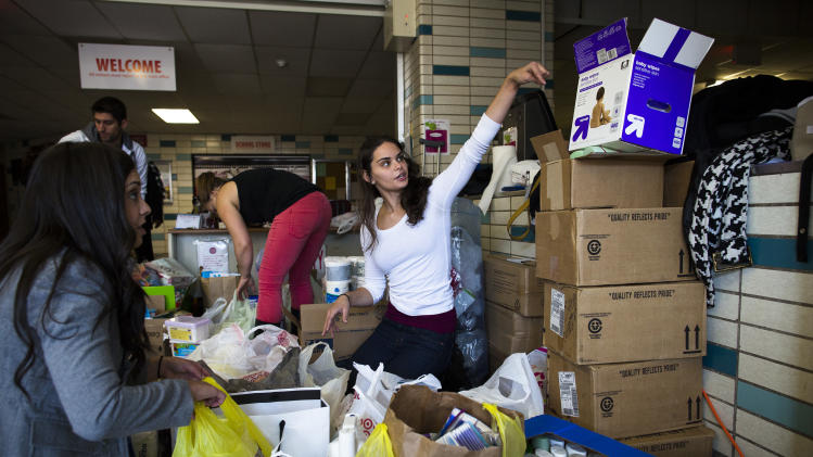 Volunteer Jamie d'Amico, 25, of Fort Lee, helps sort through donations at Hoboken High School as surrounding neighborhoods remain without power due to damage caused by Superstorm Sandy, Sunday, Nov. 4, 2012, in Hoboken, New Jersey. About 1 million homes and businesses across New Jersey are still without electricity due to Superstorm Sandy on Sunday, and officials say many of those customers may not have service restored until Wednesday. (AP Photo/ John Minchillo)