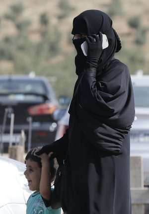 A Syrian refugee uses a mobile phone as she walks with…