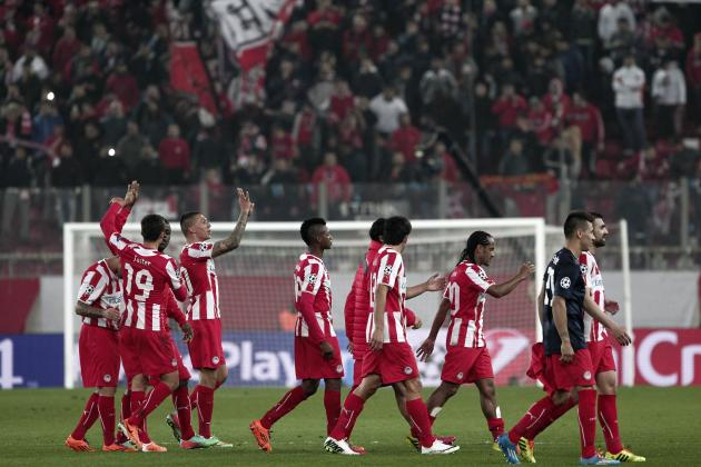 Olympiakos' players celebrate their victory over Manchester United after their Champions League round of 16 first leg soccer match in Piraeus