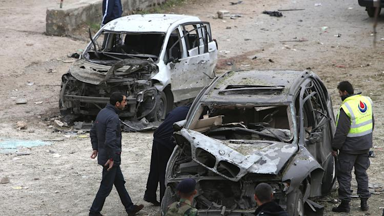 A Hezbollah civil defense worker, right, checks a damaged car at the site of a deadly car bombing Sunday night, in the town of Nabi Othman, about 30 kilometers (18 miles) north of Baalbek, northeast Lebanon, Monday March 17, 2014. Lebanese security officials said the explosion killed at least two people and caused panic and massive destruction in the Hezbollah stronghold, which has a sizable Christian population in addition to Shiites. The civil war in neighboring Syria already has ignited polarizing sectarian tensions between Lebanon's Sunnis and Shiites. (AP Photo/Hussein Malla)