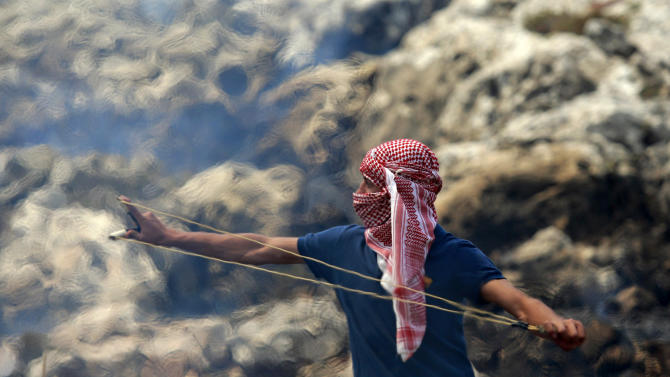 AP10ThingsToSee - A Palestinian man uses a slingshot to hurl stones at Israeli forces as tear gas fumes swirl in background, during a protest against the expansion of the nearby Jewish settlement Ofra outside the village of Deir Jarir near Ramallah, Friday, May 17, 2013. (AP Photo/Majdi Mohammed)