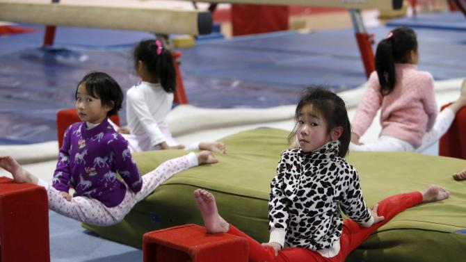 Young students stretch during a gymnastics training session at a sports school in Jiaxing
