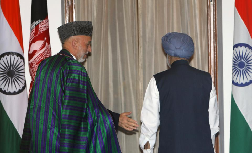 Indian Prime Minister Manmohan Singh, right, and Afghanistan President Hamid Karzai proceed for a meeting in New Delhi, India, Tuesday, Oct. 4, 2011.  Karzai is on a two-day official visit to India.(AP Photo/Gurinder Osan)
