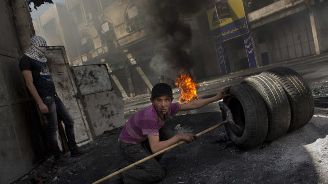 A Palestinian protester prepares to set wheels on fire, during riots against Israeli forces, not pictured, after the death of Maysara Abu Hamdiyeh at an Israeli jail, in the West Bank city of Hebron, Wednesday, April 3, 2013. Palestinian prisoners have been rioting and hunger striking since a 64-year-old prisoner died of throat cancer on Tuesday. The Palestinians have blamed Israel for the man's death, saying he was not given proper medical care. The prisoner, Maysara Abu Hamdiyeh, had been serving a life sentence for his role in a foiled attempt to bomb a busy cafe in Jerusalem in 2002. (AP Photo/Bernat Armangue)