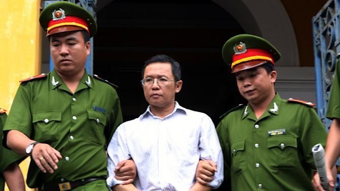 Police officers escort French-Vietnamese math professor Pham Minh Hoang out of a courthouse in Ho Chi Minh City, Vietnam, Wednesday, Aug. 10, 2011. Hoang was sentenced to three years in Vietnamese prison for belonging to a banned pro-democracy group and publishing an anti-communist blog online, his lawyer said. (AP Photo/Vietnam News Agency, Hoang Hai)