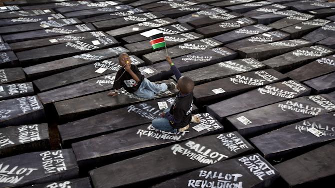 """Children of one of the protest organizers lie in the shade on top of mock coffins, on which are written """"State Burial, Ballot Revolution"""", before demonstrators carried the coffins to the Parliament and burned them, in Nairobi, Kenya Wednesday, Jan. 16, 2013. Hundreds of demonstrators angered at outgoing Kenyan legislators, whose term ended earlier this week and who earn about $175,000 a year in a country where the average annual income is $1,700, doused 221 mock coffins with gasoline, one for each legislator, to protest against last week's attempt to award themselves a $110,000 bonus, which was vetoed by the president. (AP Photo/Ben Curtis)"""