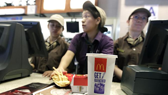 McDonald's employees serve a meal containing a large soda, Tuesday, June 12, 2012, in New York. Mayor Michael Bloomberg's proposal to ban large sugary drinks from New York City eateries is moving forward. The health board voted unanimously Tuesday to begin a public comment period on the new rule. A formal vote on approval will come later, but several board members spoke strongly in favor of the plan. (AP Photo/Mary Altaffer)