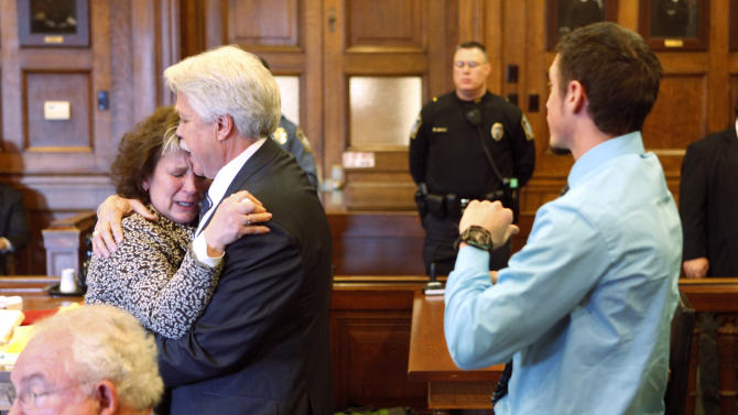 Mark Strong Sr. comforts his wife Julie after she became emotional while addressing Justice Nancy Mills during Strong's sentencing at Cumberland County Superior Court in Portland, Maine, Thursday, March 21, 2013. Strong was sentenced to 20 days in jail and a fine of $3,000 for his role in promoting a one-woman prostitution business from a Zumba studio in Kennebunk. (AP Photo/Portland Press Herald, Gregory Rec, Pool)