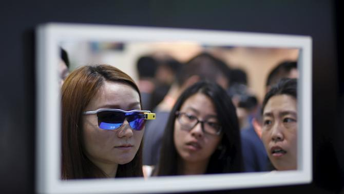 A women tries on a pair of sunglasses that has a device with a built-in optical display which allows for shooting pictures and videos during the 2015 International Consumer Electronics Show Asia in Shanghai