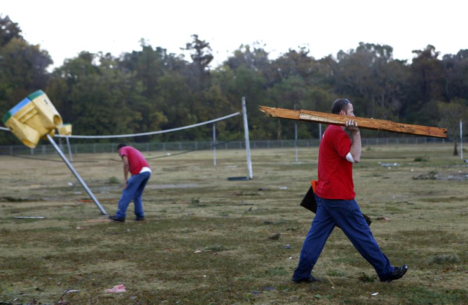 Terrebonne Parish Trustees clean up storm debris left by strong winds from a suspected tornado Wednesday, Nov. 16, 2011 at Village East School in Houma, La.   No one was injured. (AP Photo/The Houma Courier, Julia Rendleman)