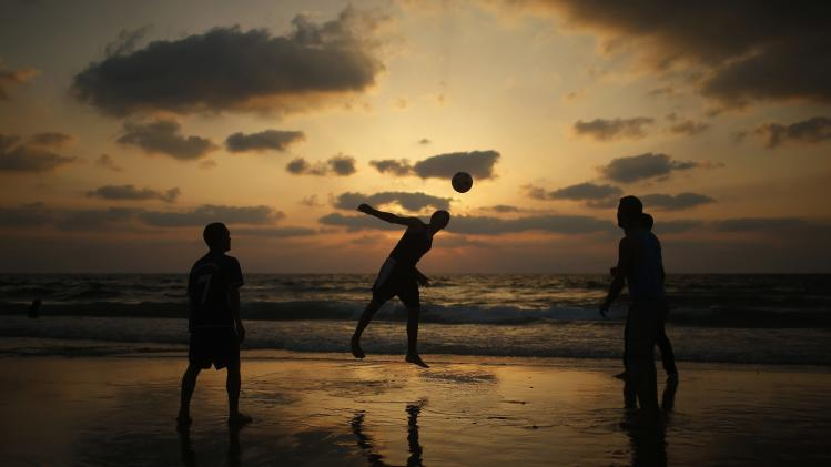 Palestinian children play football on the beach in Gaza City